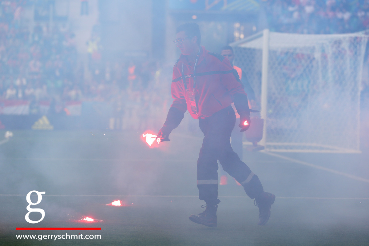 A Volunteer cleans of the pitch after Croatian fans threw pyro on the pitch